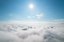 Aerial Shot Of White Fluffy Clouds And Some Blue Sky In The Distance While Flying Above The Clouds. Aerial Background. Beautiful Cumulus Clouds Captured By A Drone.