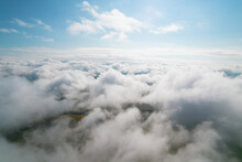 Cumulus Clouds, Aerial Background. Aerial Shot With Top View Of White Fluffy Clouds Gathering. In Between The Clouds The Ground Is Visible Here And There.