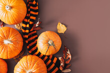 Beautifully Arranged Pumpkins With Yellow Leaves And Striped Scarf On Brown Background