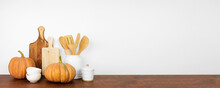Autumn Theme Kitchenware And Utensils With Rustic Pumpkins On A Wooden Shelf Or Counter. Banner Against A White Wall Background With Copy Space. Fall Home Kitchen Cooking Decor.