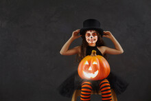 Child Having Fun On Halloween. Portrait Of Kid In Spooky Costume. Happy Girl With Beautiful Skull Makeup Looking At Camera Sitting With Cute Smiley Festive Jack-o-lantern On Dark Copyspace Background