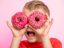 The Teenager Was Having Fun With Donuts Looking Through Them. A Boy Is Having Fun With Donuts On A Pink Background. Fun Time With Food