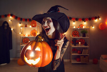 Portrait Of Woman In Wicked Witch Costume. Beautiful Lady In Black Pointed Hat With Happy Excited Face Expression Standing In Dark Room, Holding Halloween Jack-o-lantern Pumpkin, Shaking Finger At You