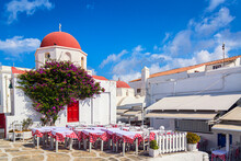 Famous Old Town Narrow Street With White Houses, Bougainvillea Flower And Red Church. Mykonos Island, Greece