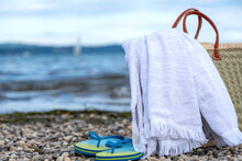 Wicker Basket, Towel And Slippers On A Rocky Beach Against A Beautiful Sky
