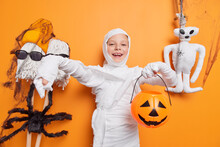 Glad Small Kid Pretends Being Ghost Or Mummy Holds Halloween Carved Pumpkin Stands Against Orange Background Poses Near Spooky Toys Says Boo. Autumn Holiday On 31st October. Scary Special Day