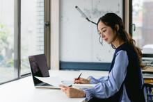 資料を手にして働く女性(自宅・テレワーク・オフィス)