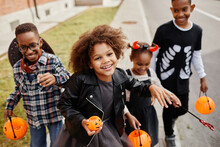 Group Of Smiling African-American Kids Trick Or Treating Outdoors And Walking To Camera Holding Pails
