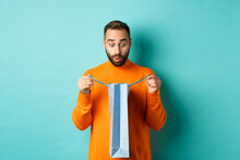 Surprised Man Open Shopping Bag And Looking Amazed, Receiving Gift On Holiday, Standing Over Turquoise Background