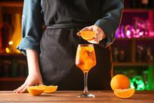 Woman Decorating Glass Of Aperol Spritz Cocktail With Orange On Dark Background