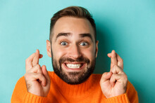 Headshot Of Hopeful Bearded Man Making A Wish, Smiling And Holding Fingers Crossed For Good Luck, Standing Over Light Blue Background