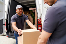 Delivery Man Looking At Colleague While Unloading Box From Moving Van