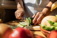 Senior Woman Cutting Cucumber In Kitchen