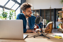 Smiling Male Freelancer Podcasting While Sitting At Desk In Small Office