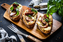 Tasty Sandwiches - Baked Bread With Camembert, Basil Pesto And Sun Dried Tomatoes On Wooden Table