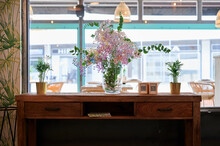 Decorative Wooden Table In Restaurant With A Glass Vase Full Of Dried Flowers And Fake Qr Codes