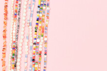 Necklaces Made From Colorful Beads And Pearls On A Pink Background With Copyspace.