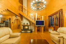 Modern Living Room Of A Log Cabin, Decorated With Wood. A Stylish Fireplace, A Chandelier And Comfortable Beige Sofas.