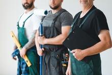 Crew Of Three Professional Builder Wearing Overalls Standing In Empty Interior