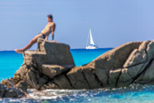 Man Sunbathing On A Rock Against Sailboats In Vibo Valentia, Calabria, Southern Italy