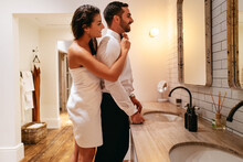 Young Woman Adjusting Her Husband's Tie In A Hotel Room