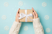 First Person Top View Photo Of Girl's Hands In White Sweater Holding Craft Paper Giftbox With White Ribbon Bow Over Big Decorative Snowflakes And Shiny Sequins On Isolated Pastel Blue Background