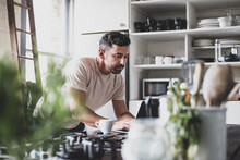 Mid Adult Hispanic Male Using Laptop In Kitchen