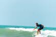 Mężczyzna surfer płynący na fali na tle błękitnego oceanu i nieba.