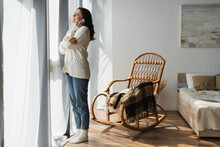 Full Length View Of Woman In Jeans And White Cardigan Calling On Smartphone Near Window And Wicker Chair