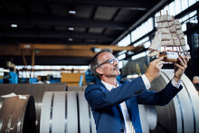 Businessman Holding Sailboat Toy At Steel Mill
