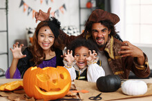 Happy African American Family Parents And Little Boy Son In Halloween Costumes Making Jack O Lantern