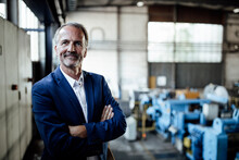 Male Business Professional With Arms Crossed Standing At Metal Industry