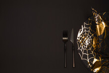 Halloween Holiday. Serving On A Dark Table With A Black Pointed Conical Witch Hat And Black Cutlery. Flat Lay, Top View Trendy Holiday Concept. Copy Space.