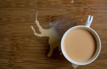 Milk Tea In White Cup With Brown Wood Background Having A Splashed  Or Spilled Tea Top View, Selective Focus