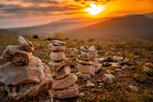 A Stone Stack With Balanced Stones On A Blurry Background Of Mountains At Sunset