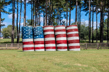An American Flag Is Painted Across A Stack Of Large Round Hay Bales In A Farm Field Against A Backdrop Of Pine Trees And Blue Sky.