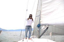 Latino Adult Man Drives A Sailboat On The Lake With Sails Unfurled As A Physical Activity, Sport And Hobby To Relax For The Weekend