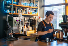 Asian Man Barista Using Coffee Grinder Machine Grinding Roasted Coffee Beans At Cafe. Male Coffee Shop Owner Brewing Black Coffee Serving To Customer. Small Business Restaurant Food And Drink Concept