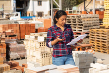Woman Manager Keeps Records Of Building Materials In The Open Area Of A Construction Store