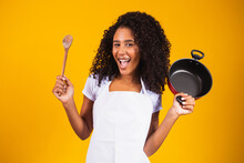 Cooking Utensils. Cooking Woman In Kitchen With Frying Pan And Wooden Spoon. Housewife Dancing..