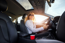 Happy Caucasian Woman With Blond Hair Driving Modern Car During Sunny Day. Pleasant Mature Lady In Sunglasses And Formal Clothes Seating On Drivers Seat And Fastening With Belt.