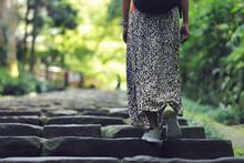 石の階段をのぼる女性の足元