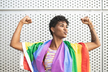 Young Lesbian Woman Flexing Muscles With Rainbow Flag