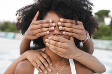 Young Female Friends Covering Mouth And Eyes Of Afro Woman