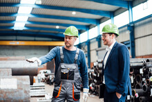 Warehouse Worker Discussing Over Pipe With Male Manager In Industry