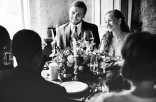 Bride And Groom Clinging Wineglasses With Friends On Wedding Reception