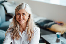 Smiling Mature Woman With Long Gray Hair In Coffee Shop