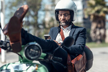Male Professional Using Mobile Phone While Sitting With Feet Up On Scooter