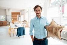 Smiling Businessman Holding Golden Star Shape Balloon In Office