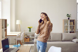Girl feeling happy. Joyful young woman receives good news during pleasant conversation on mobile phone at home. Woman with a sincere wide smile saying yes. Concept of success and luck.